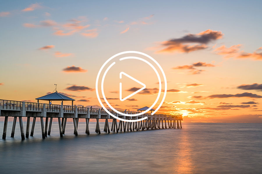 Juno Beach Pier during sunrise with play button overlay